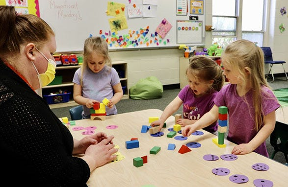 Staff member Kaitlynn Alward (from left)  counts with Emma Nowka, Abby Nowka and Ensley O'Neal at Training Wheels Childcare Center in East Jordan.