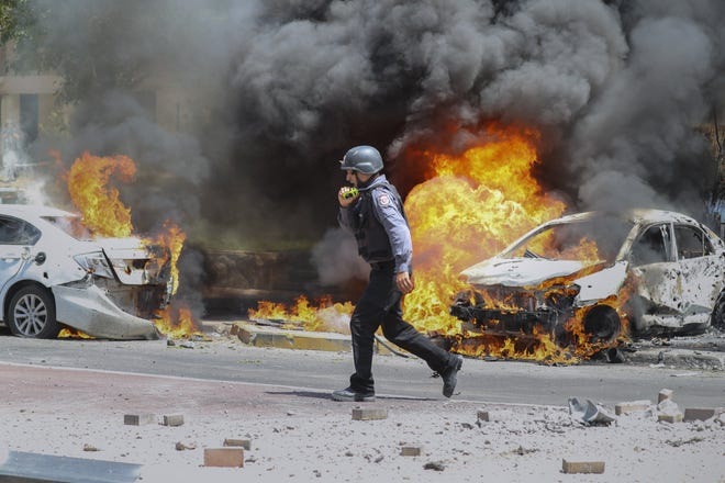 An Israeli firefighter walks next to cars hit by a missile fired from Gaza Strip, in the southern Israeli town of Ashkelon, on Tuesday.