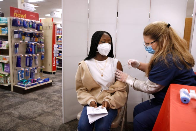 Meta Konte, a 17-year-old North Providence High School student, watches closely as technician Victoria Connolly administers Konte's first COVID-19 vaccine shot at the CVS on Manton Avenue in Providence on Thursday afternoon.