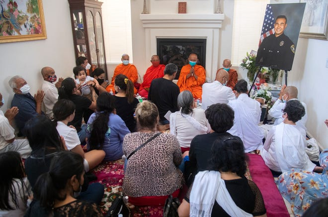 Buddhist monks from the Wat Dhammararam Buddhist Temple perform a blessing ceremony Wednesday evening in front of friends and family at the home of Lee Inn, father of Stockton police Officer Jimmy Inn, who was killed in the line of duty during a domestic dispute call on Tuesday.
