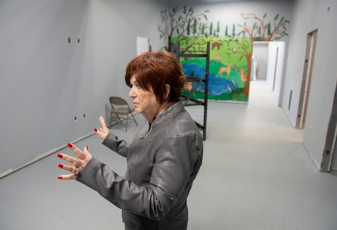 Anne Marie Noble, The Haven of Portage County executive director, leads a tour during an open house for shelter that is set to open in September. Noble stands in the women dormitory space with a mural designed by Janis Mars Wunderlich.
