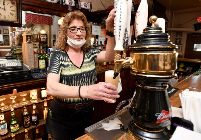 Owner Robin Muntean pours a beer at Arcadia Grille in downtown Canton.