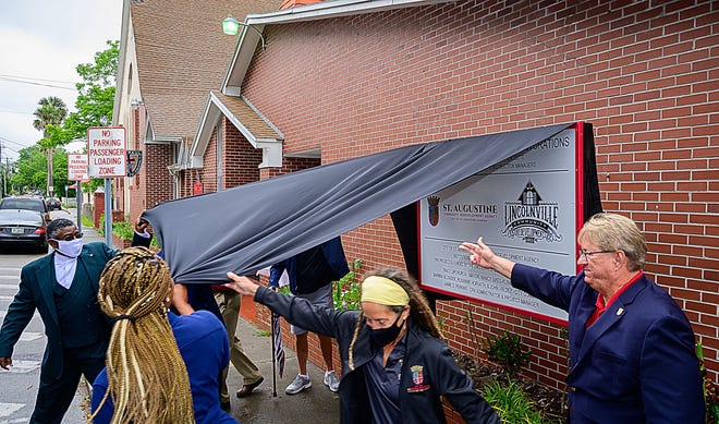Church members and city officials unveil a sign in front of St. Paul AME Church in the St. Augustine community of Lincolnville on Thursday during a ceremony announcing a $350,000 project to replace the church's roof and make other repairs that are being funded by the Lincolnville CRA's Institutional Rehabilitation program.