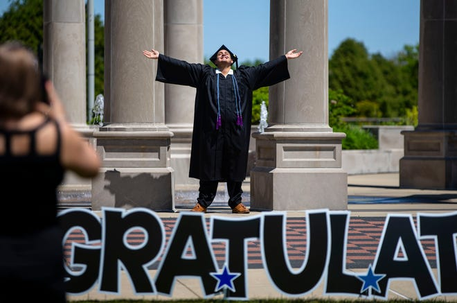 """Oscar Mercado of Palatine celebrates his graduation next to The Colonnade before heading inside the UIS Performing Arts Center for the """"stage experience"""" for the 2021 Commencement Ceremony at the University of Illinois Springfield on Thursday. UIS is holding 52 individual """"stage experiences"""" over two days for the Class of 2021 with eight students in each ceremony to allow them to walk the stage in their cap and gown."""