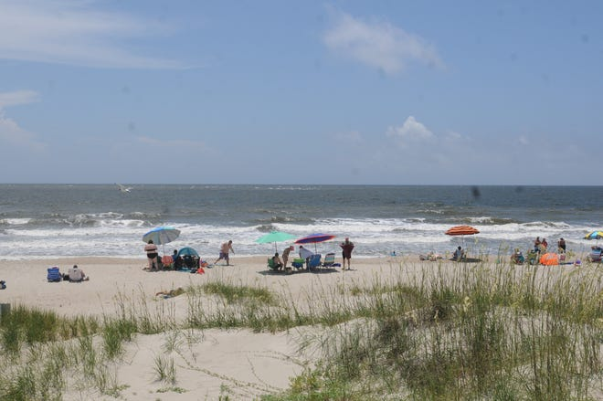 People enjoying nice weather on the beach in Oak Island, N.C.