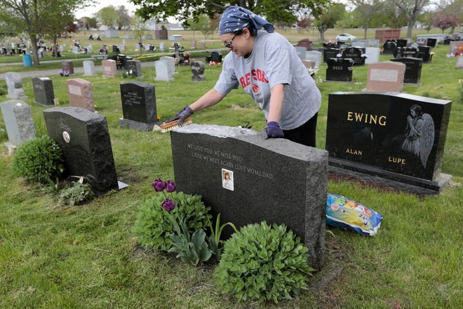 Nancy Pires cleans the gravestone of her sister Margaret Pires and the gravestone of her parents, left, at Rural Cemetery on Dartmouth Street in New Bedford.