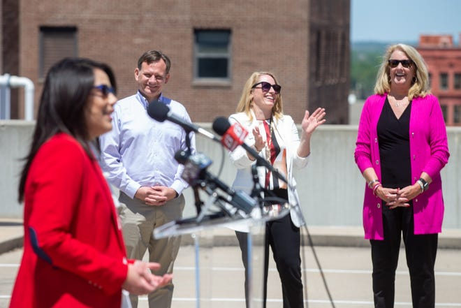 Topeka mayor Michelle De La Isla cracks ups, from right, Bonnie Speaks, Lawrence Chamber of Commerce president; Kirsten Flory, Lawrence Chamber board member; and Lawrence Mayor Brad Finkeldei during a special announcement regarding a joint trip to northwest Arkansas.
