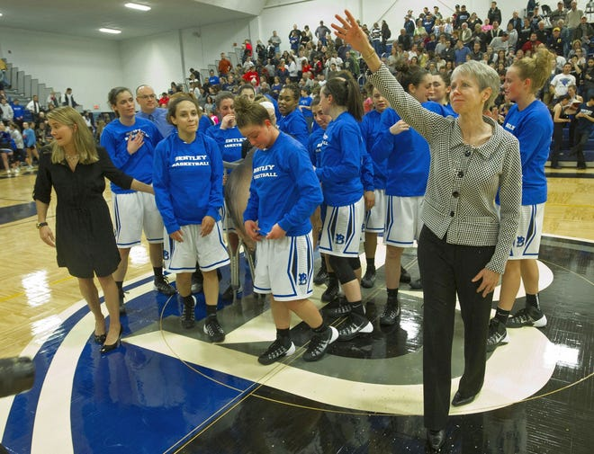 Bentley University basketball coach and Southbridge native Barbara Stevens waves to the crowd after becoming the sixth coach in women's college basketball history to record 900 victories when her Falcons defeated St. Anselm College on Jan. 24, 2014.