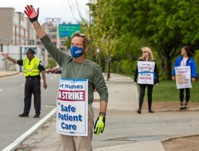 Nurse Ed Adamiak waves to passing cars while walking the picket line Thursday outside St. Vincent Hospital.