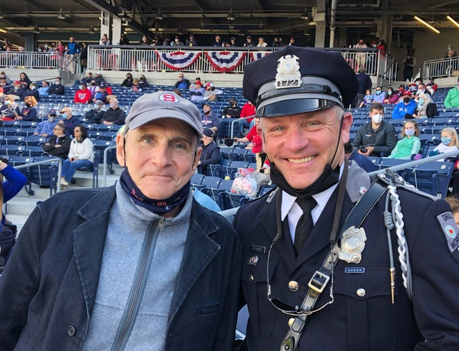 """From left, James Taylor and Worcester Police Officer Thomas Hurley have one thing in common: They both sang during WooSox opening day at Polar Park. Taylor sang the national anthem while Hurley sang """"God Bless America."""""""
