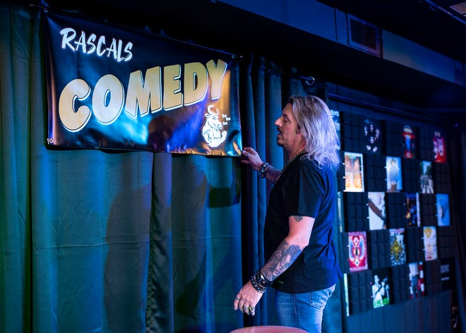 Frank Pupillo, co-owner of Rascals in Worcester, adjusts a banner while preparing for an upcoming comedy show Thursday.