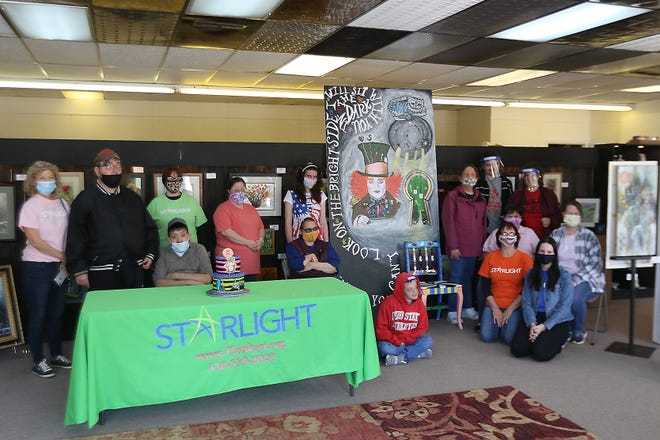 """Artists from Starlight Enterprises, Inc. and their coaches are shown Thursday with the """"Alice in Wonderland"""" mural they painted. It will be installed within two weeks on the front of the building housing the TuscArts Cooperative gallery and Around the Corner Frames."""