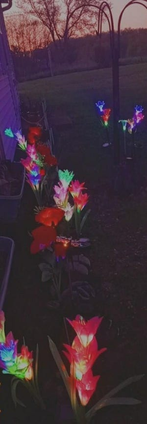 """The family lit solar flowers """"planted"""" in cowboy boots in memory of Sister Susan."""