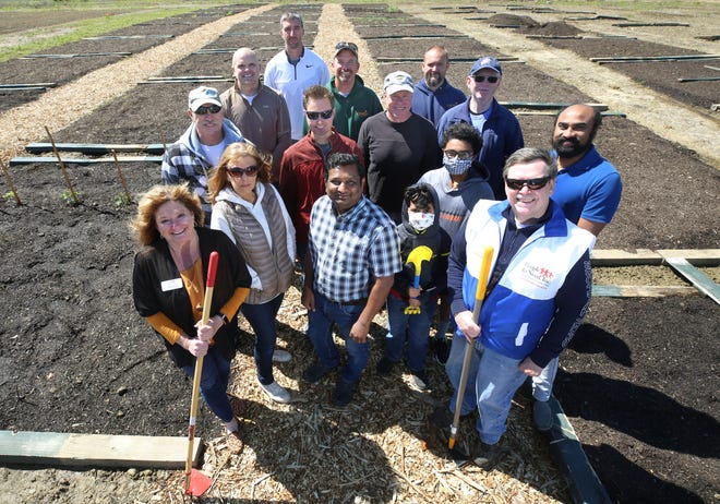 Representatives from People In Need Inc., Orange Township and urban gardeners kneel together at the new community garden in the Evans Farm development. Pictured are (front row, from left) Kathy Hoff, executive director of People In Need; Diane Norcia, Srini Gunda, Ketch Dandangi, 7; Jim Lewis, past board president of People In Need; (second row) Gary Norcia; John Muirhead-Gould; Jamie Stabl; Rushil Dandangi, 13; Mark Morrisson; Kalyan Dandangi; (back row) Orange Township trustee Ben Grumbles; Silas Bowers, the township's director of operations; Aaron James, roads and parks manager; and David Gilson, roads worker.