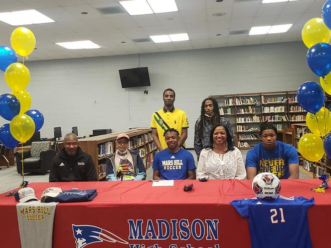 Nehemiah Barnette poses with family and friends after committing to play soccer at Mars Hill University.