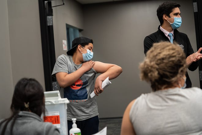デトロイトのガブリエルバスケス(左)、13歳、デトロイトの母親インディラシスネロン(右)が木曜日にデトロイト南西部の理想的なグループのワクチンクリニックで最初の予防接種を受けたときに座っているときに、順番を待っている間にどの腕を使用するかを確認します、2021年5月13日クリニックは一般に無料で、全米腎臓財団、ヘンリーフォードヘルスシステム、イデアルグループが主催しました。