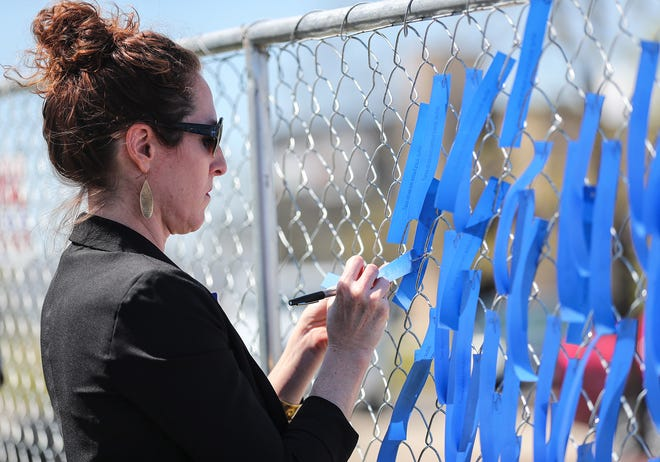 Kelly Norton of Grande Cheese writes on a donor ribbon Thursday, May 13, 2021 in front of the construction site of the future St. Katharine Drexel Shelter building on Peters Ave. in Fond du lac, Wis. Donors of the shelter are honored with a display of ribbons in front of the new building construction. The shelter will be the first stand-alone shelter for homeless people in Fond du Lac. Doug Raflik/USA TODAY NETWORK-Wisconsin