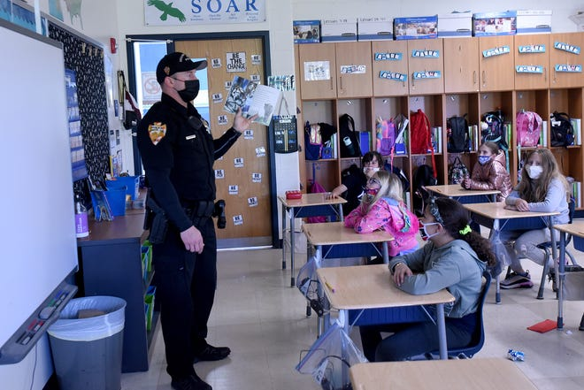 Newark Police Department Officer Steven Carles reads a book about tigers to Tosha Cooperrider's third grade class on Wednesday, May 12, 2021 at Hillview Elementary School. Carles has read to 60 classes in the Newark School District as part of the Books & Badges program through Starfish Assignment.