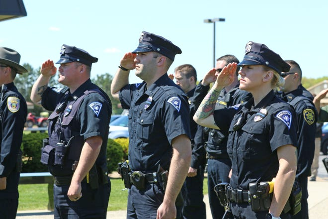 From left, Curt Cochran, Devin Woods and Amy Pugh of the Port Clinton Police Department offer a salute during the playing of Taps at a police memorial ceremony held Thursday at the Carroll Township Service Complex. The event was part of National Police Week, which runs through Saturday.