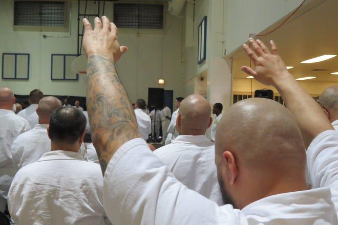 Allred Unit inmates worship at a service held in a gym at the prison.