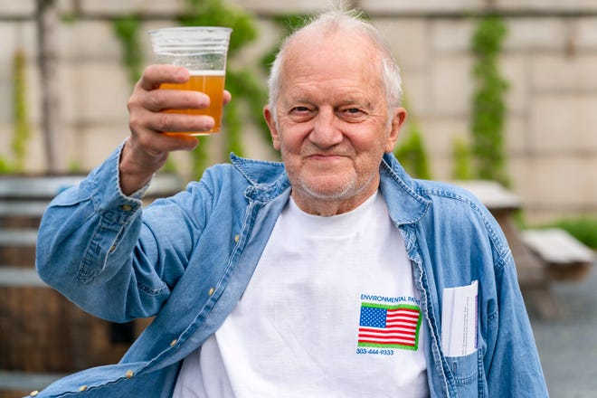 After getting the Johnson & Johnson vaccine on May 6, 2021, at the Kennedy Center's outdoor cafe in Washington, D.C., George Ripley, 72, holds up his free beer.