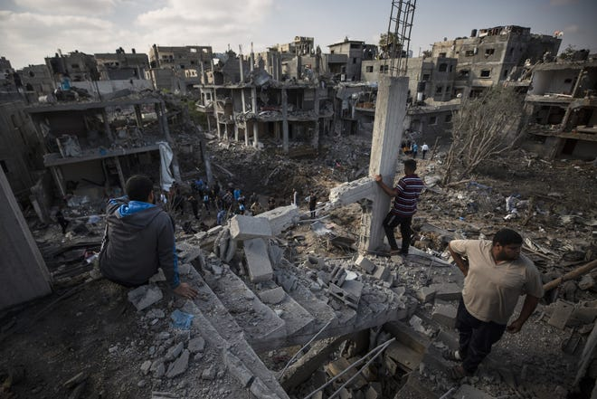 Palestinians inspect their destroyed houses following overnight Israeli airstrikes in town of Beit Hanoun, northern Gaza Strip, Friday. [AP PHOTO/KHALIL HAMRA]