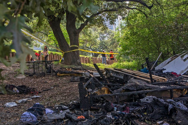 People jog past a homeless encampment that caught fire along the Ann and Roy Butler Hike-and-Bike Trail in downtown Austin Friday.