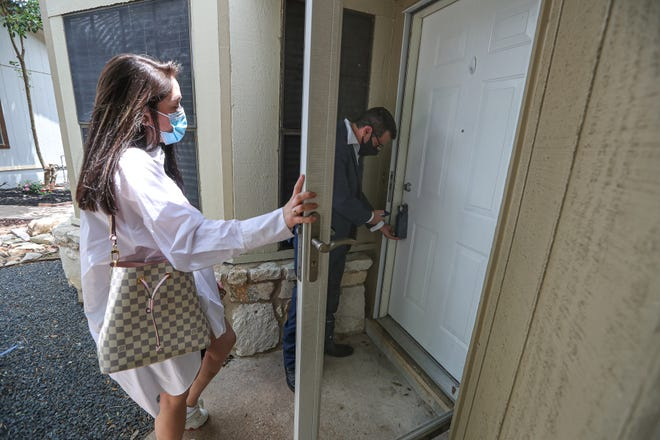Real estate agent, Mike Gonzalez, right, opens the front door for prospective buyer Maria Villarreal at a home for sale in South Austin last week. The Central Texas housing market has once again set records for sales and median prices, the Austin Board of Realtors announced Tuesday.