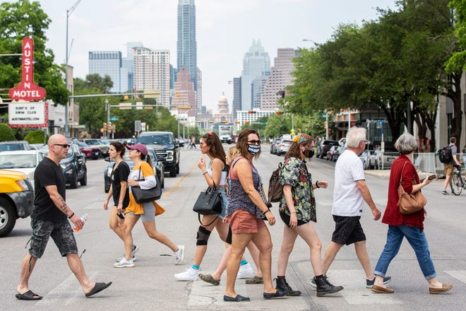 Masked and mask-less visitors cross South Congress Avenue in Austin on Friday, May 14, 2021. The C.D.C now says it is safe for fully vaccinated people to take their masks off in most indoor and outdoor settings.