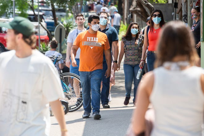 Masked and maskless visitors cross South Congress Avenue last month. The CDC says it is now safe for fully vaccinated people to take their masks off in most indoor and outdoor settings.