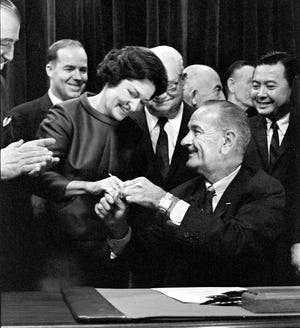 President Lyndon B. Johnson hands a signing pen to Lady Bird Johnson at the signing of the Highway Beautification Act in the East Room of the White House, Oct. 22, 1965. Although she was most identified with this law, Lady Bird had a hand in almost everything political in LBJ's career.