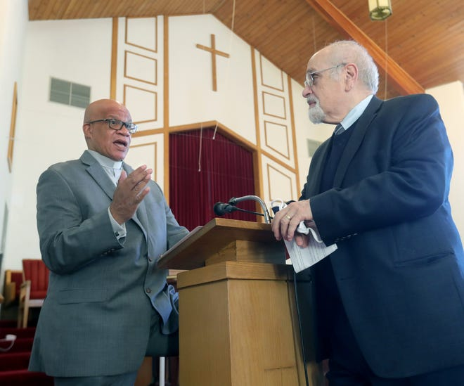Rev. Gregory Harris, left, and Martin Belsky, Chairman of the Jewish Community Council talk Thursday before a gathering of local interfaith leaders at Antioch Baptist Church in Akron.
