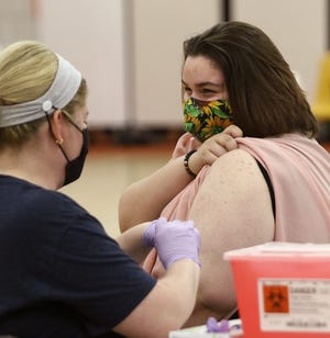Marlington High School freshman Sophia Vigliotti, 15, (right) speaks with nurse Cynthia Sheets moments after receiving the first of two Pfizer COVID-19 doses inside Marlington Middle School's gym.