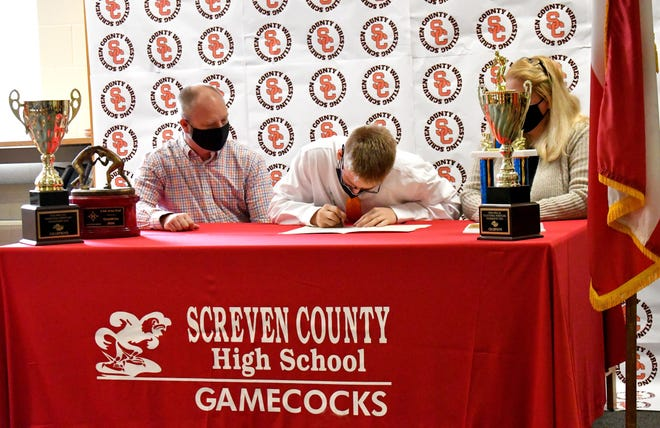 With his parents Donny and Kit Thompson watching, Screven County's Cody Thompson signs his letter of intent with Brewton-Parker College on May 13 in the media center at the high school. Thompson, who topped 100 wins in his career, wrestled in the 152-pound class as a senior.