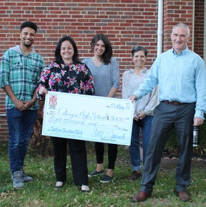 Palmyra parents hold up their big check before the May 12 Board of Education meeting. They gave one check for $8,000, shown here, and another for $1,500.