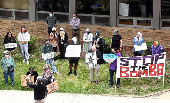 Mid-Missourians for Justice in Palestine coordinator Jeff Stack, center with bullhorn, talks to Palestinian supporters holding signs Friday during a protest of Israel in front of the Columbia Post Office.