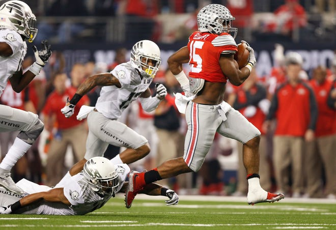 Ohio State running back Ezekiel Elliott leaves Oregon defenders behind as he runs for a touchdown in the College Football Playoff championship at AT&T Stadium in Arlington, Texas, on Jan. 12, 2015.