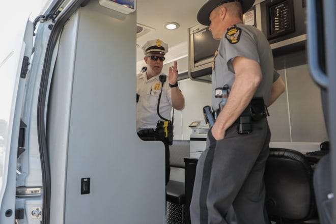 OVI countermeasures Sgt. Adam Barton, center, talks about the features of the Columbus Division of Police's new mobile breath testing vehicle on Friday at the Columbus Police Academy. The vehicle, which was purchased with money from the AB InBev Foundation, will reduce processing times of OVI stops by 60 to 90 minutes, and will allow police to do blood and breath tests of suspected intoxicated drivers in the field.