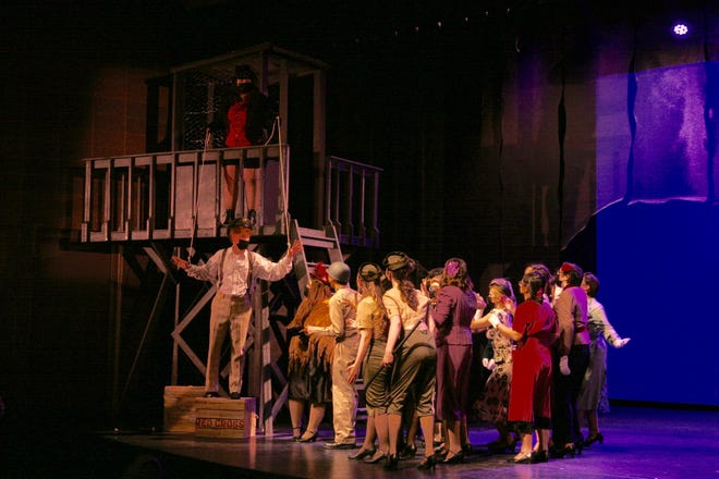 """The Leading Player, portrayed by Ella Slupe, literally pulls the strings of Pippin, played by Cole Carrico, as he addresses nobles, peasants and soldiers during a scene in Adrian HIgh School's production of """"Pippin."""""""