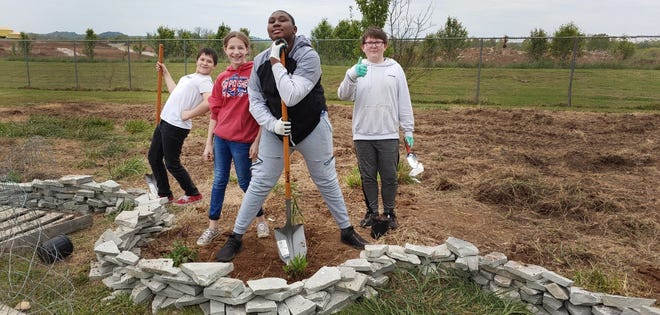Students at Spring Hill Middle School build a pollinator garden at the school campus in Spring Hill, Tenn., on Friday, April 23, 2021.