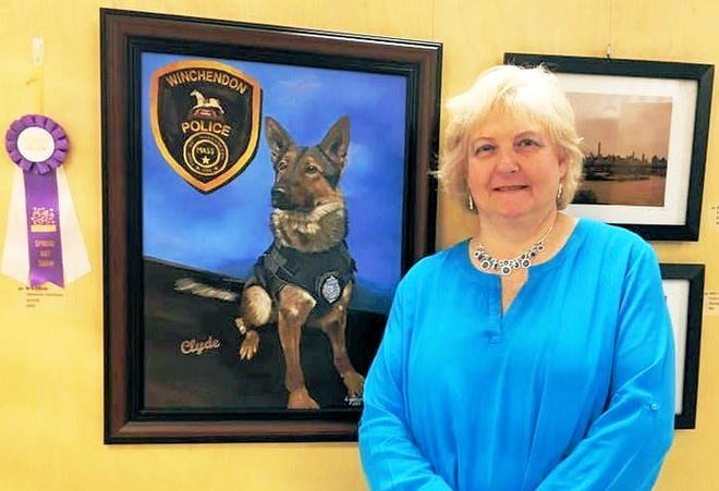Deborah Giordano, president of the Gardner Area League of Artists, is shown with her painting of K9 Clyde of the Winchendon Police Department.