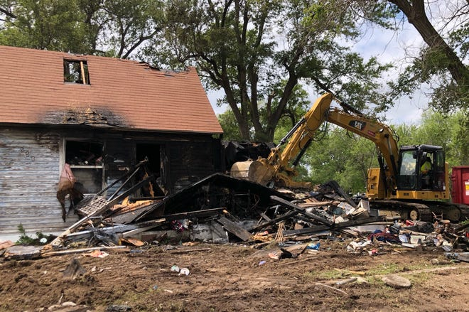 An employee of Cronus LLC of Haven operates an excavator to tear down a house at 550 Ave. D that was destroyed by fire from a lightning strike Friday morning. Fire officials wanted the house torn down immediately because so much stuff was in the house, they could not get inside to ensure the fire was fully extinguished.