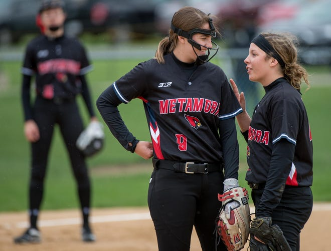 Alex Bishop, left, chats with a teammate in the pitching circle during a 2019 game against Illini Bluffs in Metamora.