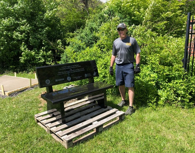 Kevin Simon, director of Mineral County Parks and Recreation, stands beside the marble bench donated to Larenim Park by the Gold Star Mothers. The bench overlooks the orchard where the county just planted 55 apple trees - one for each county in West Virginia.