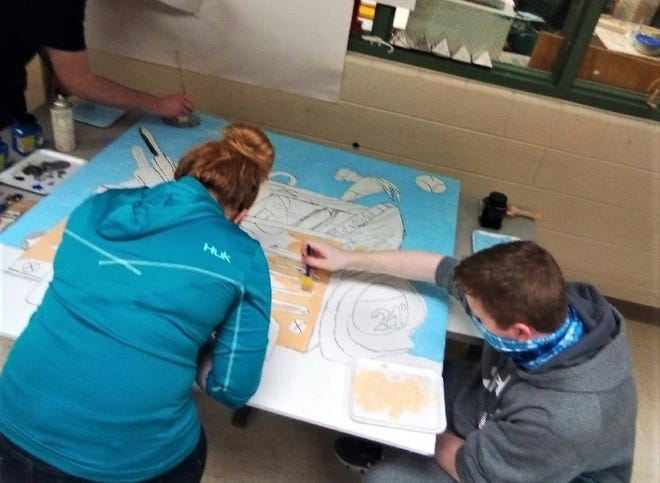 Keyser High School art students Hailey Reel and Shane McGuinness work on one of the murals to be hung outside the Mineral County Technical Center as part of a cooperative program with Highland Arts Unlimited.