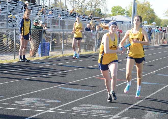 Tara Szuper gives the baton to her sister Alyssa Szuper during Airport's winning 1,600-meter relay Thursday. In the background are the other two members of the relay, Lauren Pitock and Mara Szuper. The Jets needed to win the race to pull out a 64-63 win over St. Mary Catholic Central.