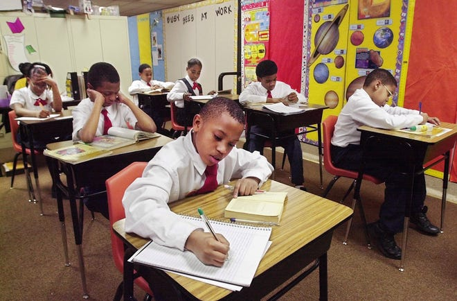 Glen Chiles and his fifth and sixth grade classmates complete an assignment at St. John Christian Heritage Academy in 2001. The private school will close this year after 32 years of operation, and a new charter school will open in the church.