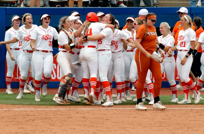 Oklahoma State celebrates after Karli Petty (14) scored the winning run in the ninth inning of a 3-2 win over Shea O'Leary (29) and Texas in the opening game of the Big 12 softball tournament Friday at the USA Softball Hall of Fame Complex .