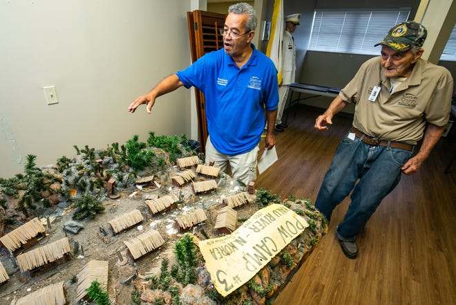 """Volunteers Carlos Gonzalez, left, and Korean War veteran Ralph Mueller, right, talk about a model of a North Korean POW/work camp that was created by the late Douglas Robinson, who was a Korean POW for 33 months. The camp model is part of the Korean War Veterans Exhibit at the Marion County Veterans Exhibit and Education Center. Mueller and others were instrumental in updating the Korean War Veterans Exhibit. Mueller and another veteran give historical info to visitors when they tour the facility, which is open Wednesdays, Thursday and Fridays from 9 a.m. to 1 p.m. """"I wanted to give a first-hand account to youngsters (when they tour the facility),"""" Mueller said."""