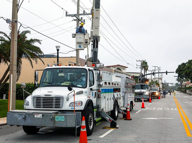 Florida Power & Light workers repair a broken power line on North County Road near Sunset Avenue as winds from Hurricane Isaias pass by the area last August. FPL crews will perform equipment upgrades along seven roads beginning Monday.